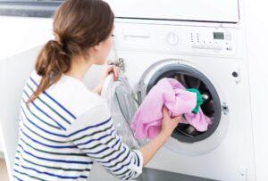 Junge Frau steckt Wäsche in die Waschmaschine