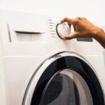 Hand dreht am Einstellungsrad einer Waschmaschine