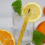 Thermometer vor einem Glas Wasser mit Zitrone und Minze