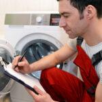 Handwerker macht sich Notizen zu defekter Waschmaschine