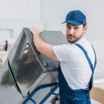 Handwerker transportieren Kühlschrank auf einer Sackkarre
