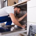 Handwerker baut Spülmaschine ein
