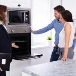 Junges Paar steht in einer Küche vor einem Backofen und lässt sich von Verkäuferin beraten