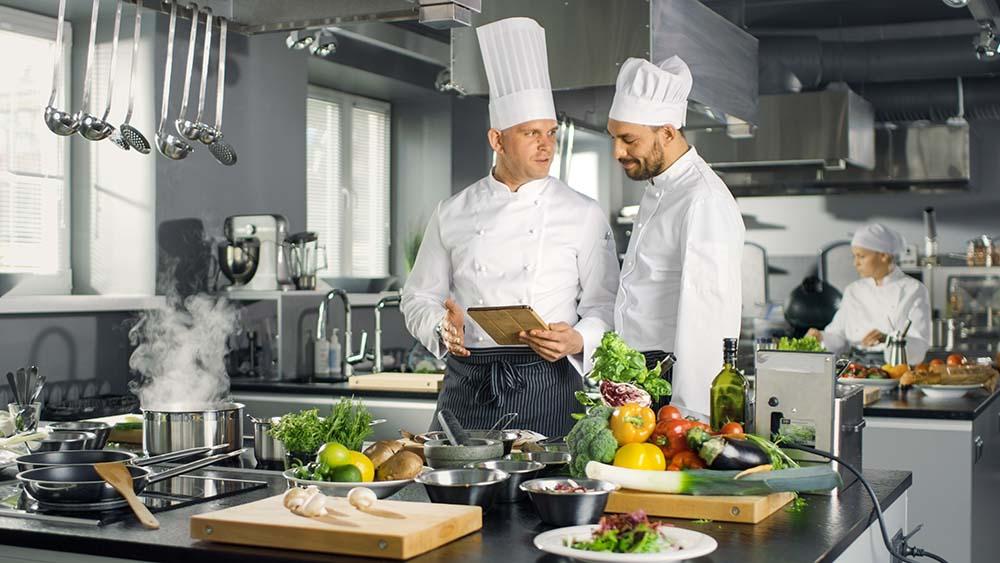 Zwei Köche schauen in einer Gastronomie Küche aufs Tablet
