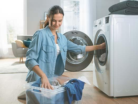 Junge Frau legt Wäsche in einen Trockner