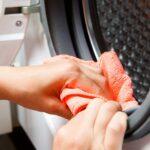 Frau reinigt Dichtung eines Trockner mit einem orangenen Lappen