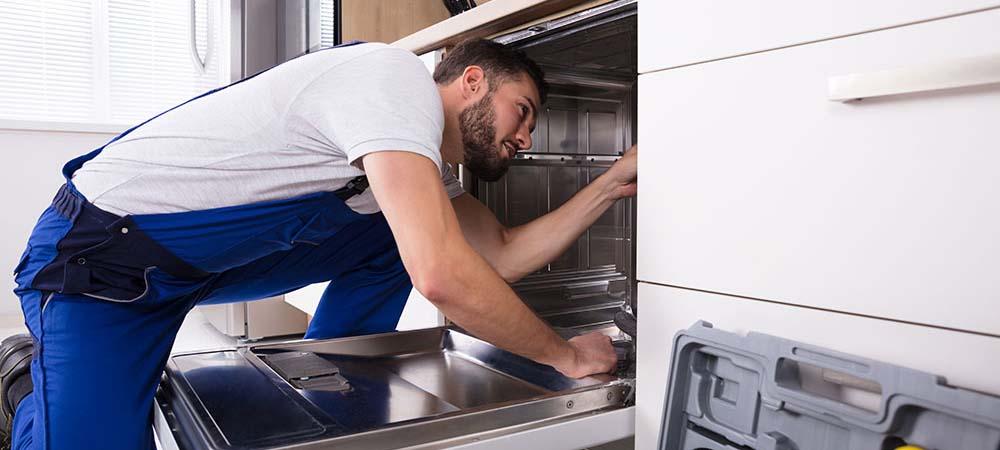 Fachmann baut Spülmaschine ein