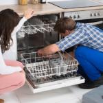 Frau schaut Handwerker beim reparieren der Spülmaschine zu