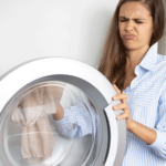 Junge Frau rümpft beim Waschmaschine säubern die Nase