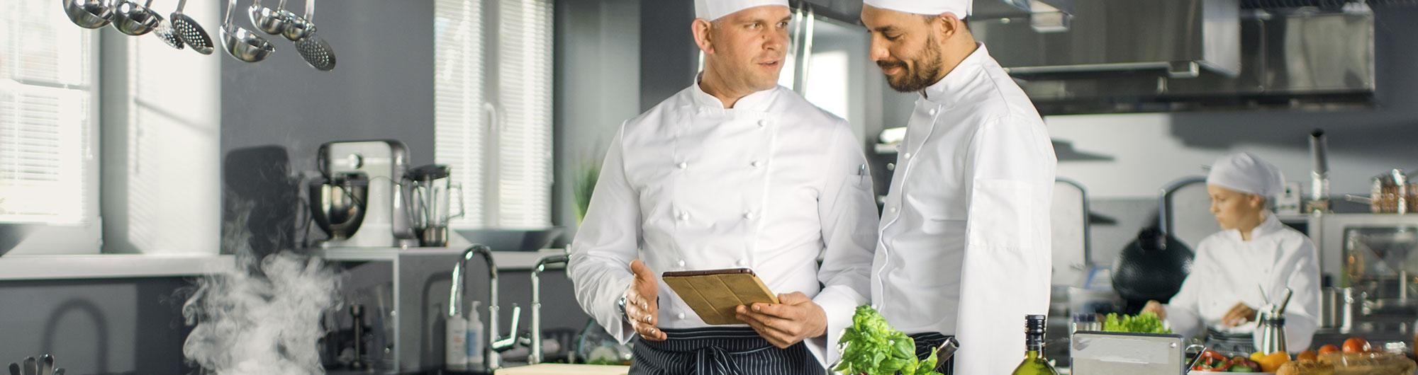 Köche besprechen Menükarte in großer Küche